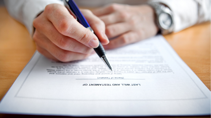 Image of a man getting ready to sign his Will